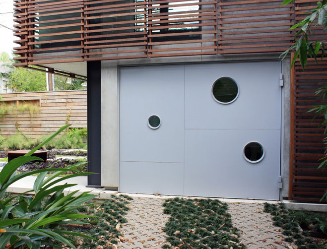 Yoga Studio And Garden View From Driveway Approach Of Custom Garage Door Side Hinge With Port Hole Window Openings